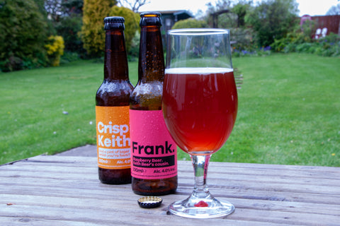 Two bottles of Keith Brewery, Crisp & Frank, with Frank poured into a glass outside.