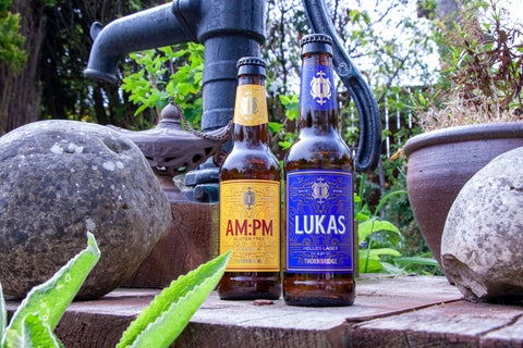 Two bottles of beer from Thornbridge Brewery, their AM:PM Session Indian Pale Ale IPA Beer, and a bottle of their popular beer Lukas. In an outside setting on top of a wooden presentation.