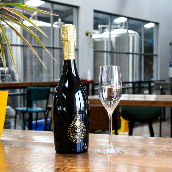 A bottle of Accademia Prosecco sat with a Prosecco glass on a table within a bar based in Newcastle, United Kingdom.