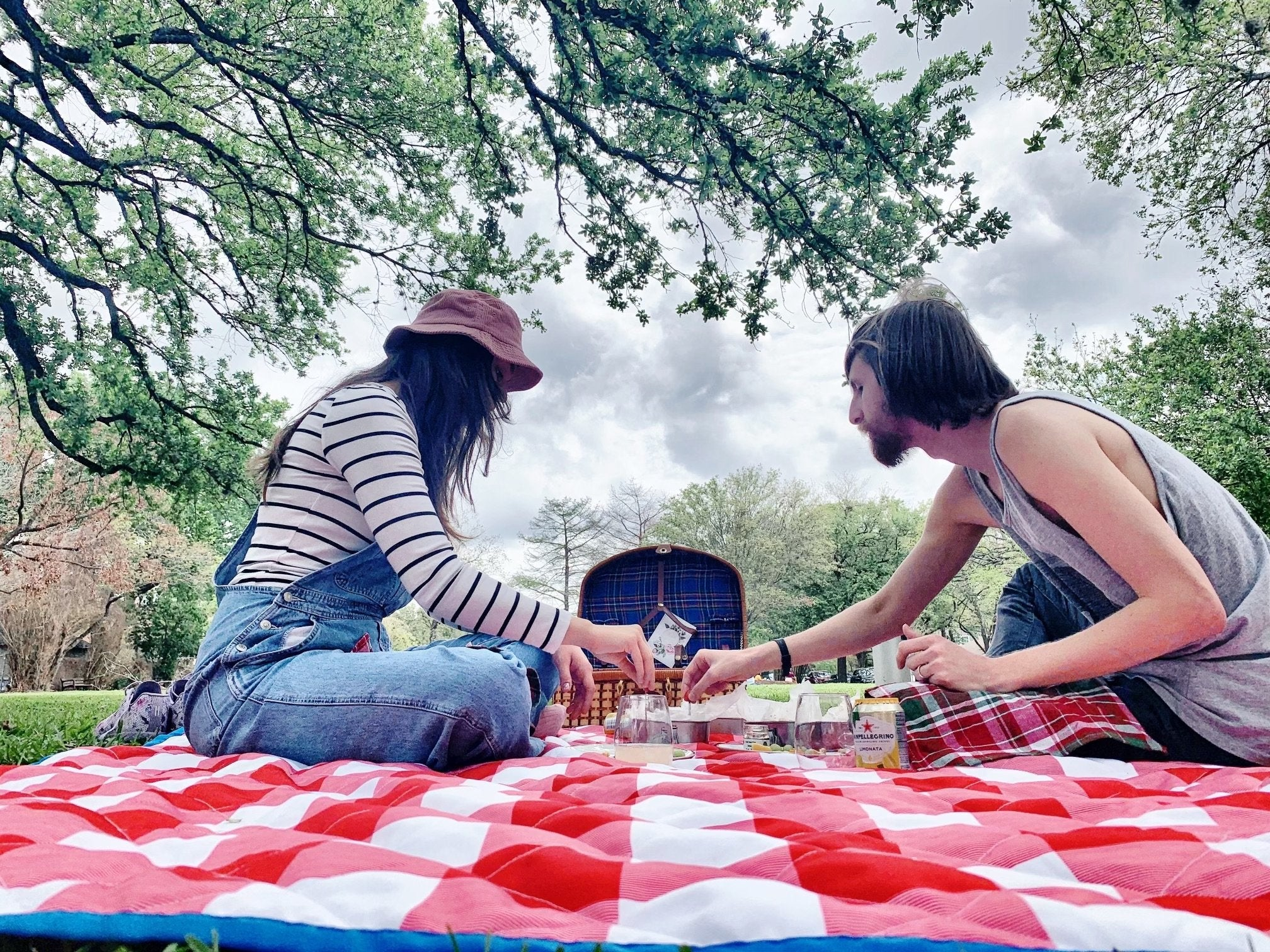 Two people on a casual picnic date with a classic red and white blanket.
