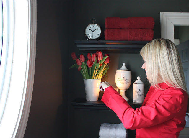 Sarah Macklem lighting a candle in front of roses