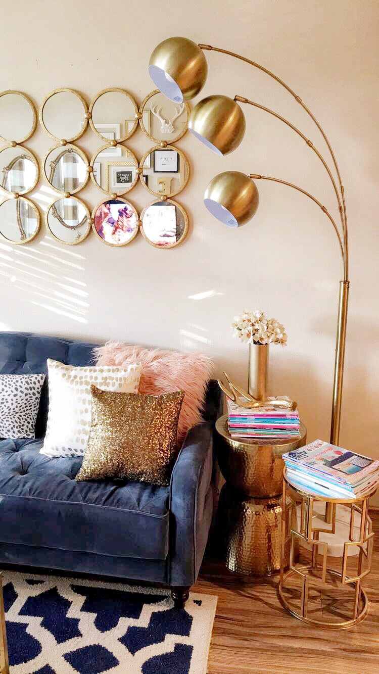 Living room with blue couch, accent pillows, mirror and gold light fixture