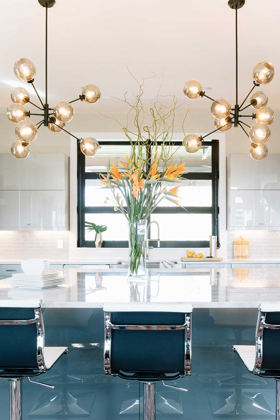 Jessica Davis' dining room with funky light fixtures, barstools, and flowers
