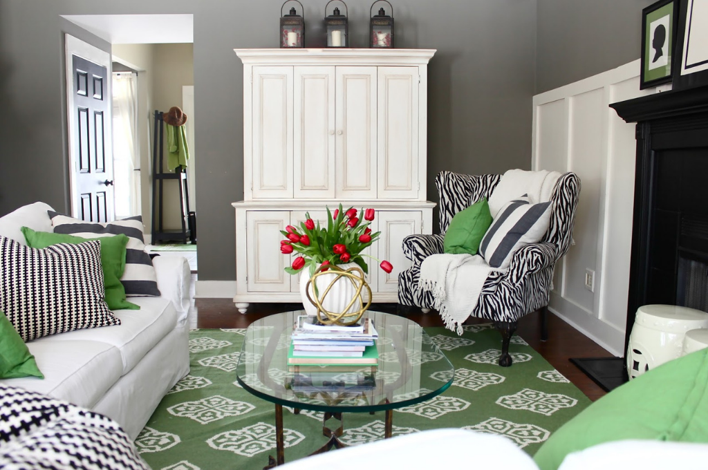 Living room with green rug, white couch, and heirloom table