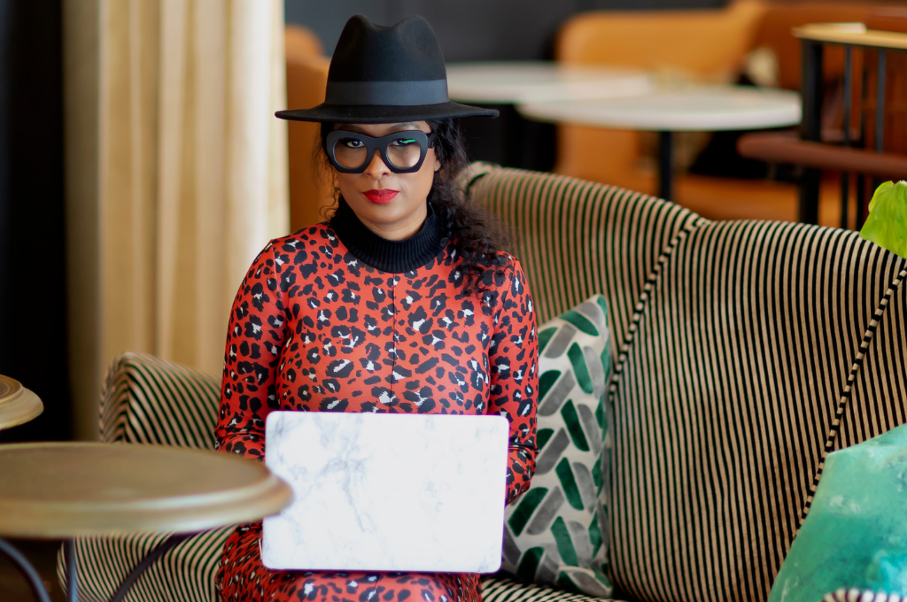 Dominique Calhoun sitting with her laptop in bold glasses and a hat