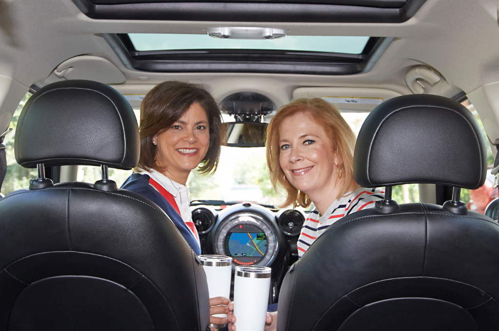 Fox and chenko smiling in car holding coffee