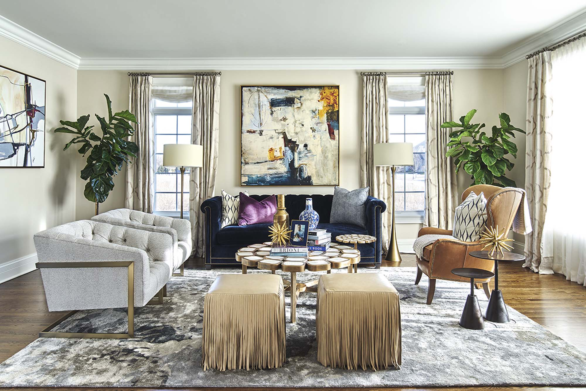 Tiffany Brooks Interiors designed a living room with gold poufs, leather chair and cream accents