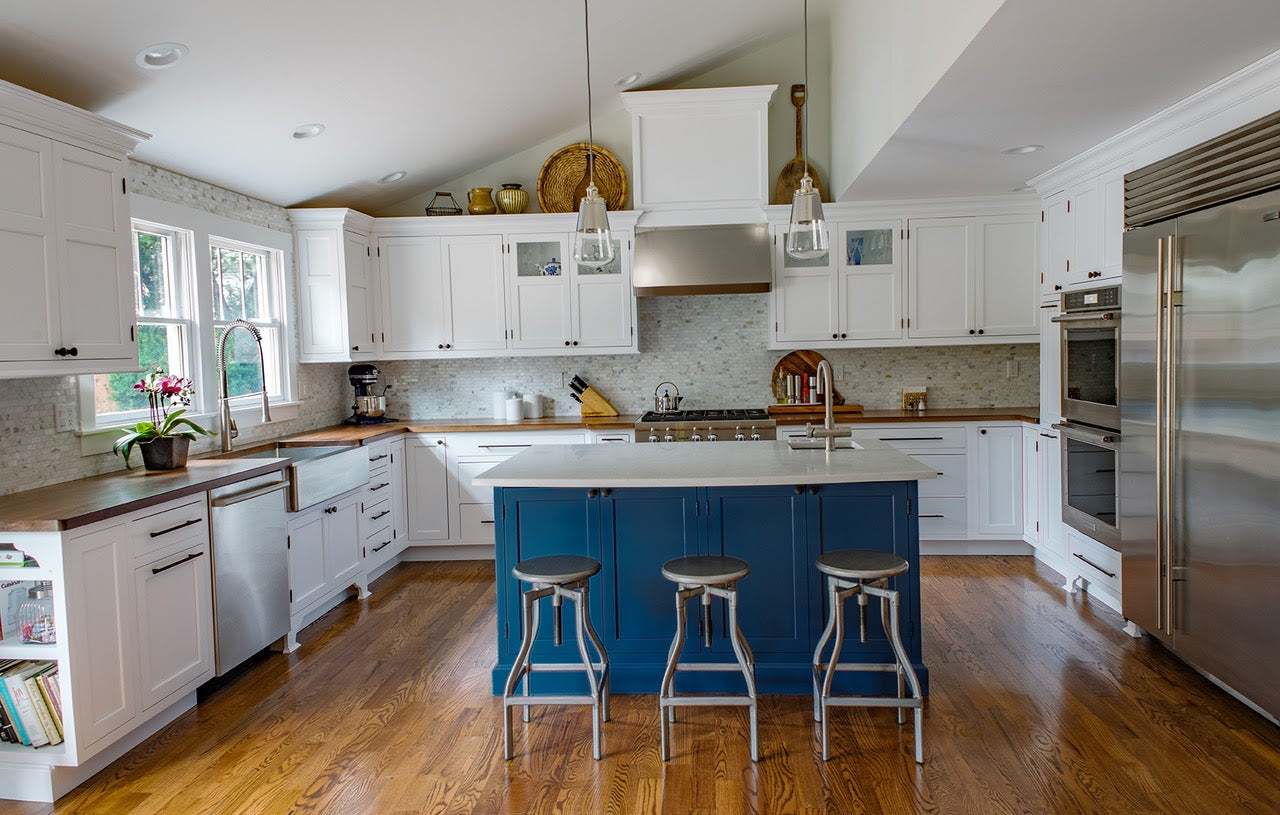 Kitchen with white cabinets, wood counters, blue island, and stainless steel appliances