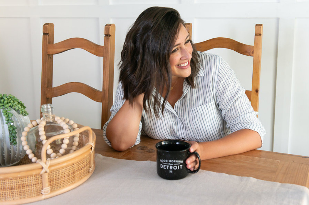 Steph Morris of North and Birch drinking coffee and smiling at a desk