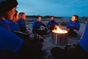 close up of team of adventurers sat around a campfire on the beach