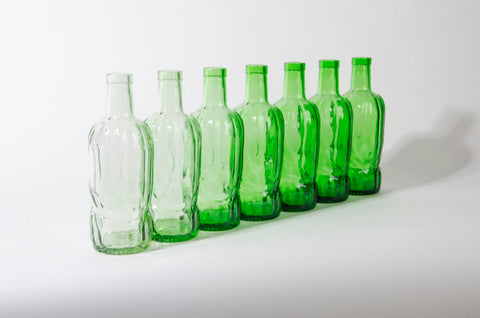 Row of River Rock whisky bottles using recycled glass in various shades of green