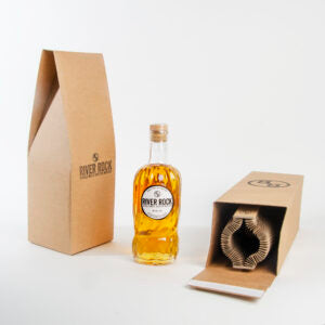 bottle of River Rock single malt whisky with branded plastic-free packaging  to the left and right