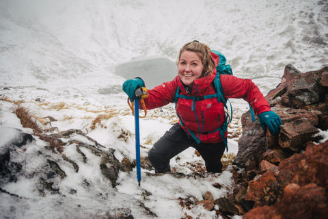 Woman wearing red jacket smiling for photo whilst climbing up a mountain