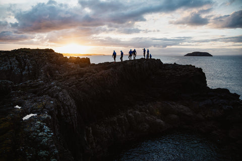 group of people in the distance standing on the coastal rock at sunset
