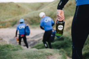 Three males hiking on a  Scottish hill, one holding a bottle of River Rock single malt whisky