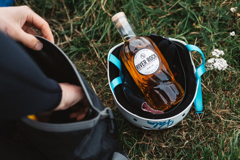 Basket on grass with bottle of River Rock single malt whisky inside, to the left a person's arm reaching into a rucksack