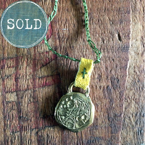 necklace: yellow bronze charm with green cord