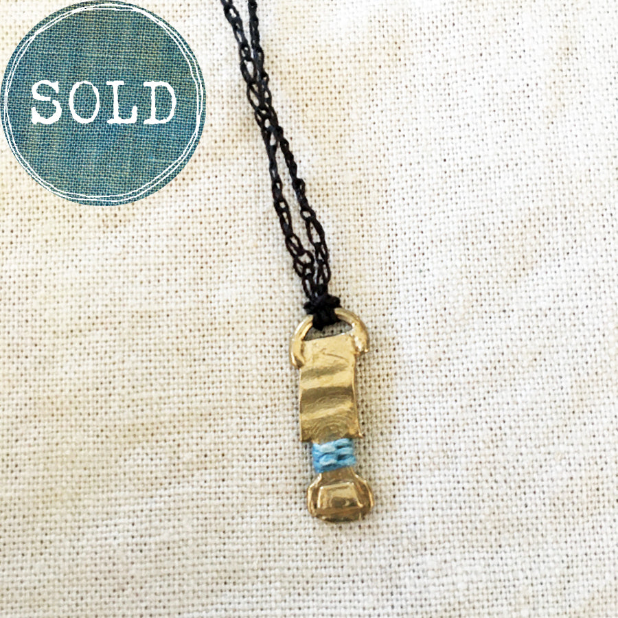 adjustable necklace: yellow bronze charm wrapped with indigo-dyed silk thread on dark brown crocheted cord