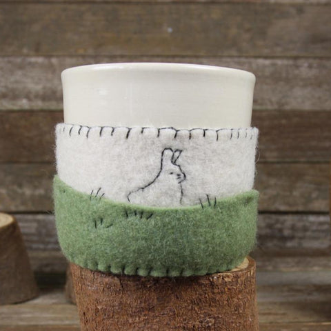cup in cozy: rabbit in field