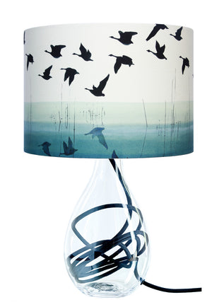 Geese flying over water lampshade on glass lamp base with black flex by Anna jacobs