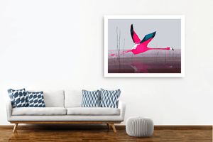 Large pink flamingo print hanging on a white wall beside a grey sofa with blue cushions