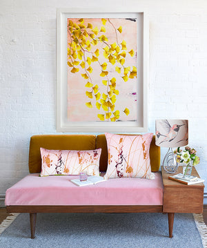 Ginko Tree branch limited edition print by Anna Jacobs hanging above pink and bronze sofa