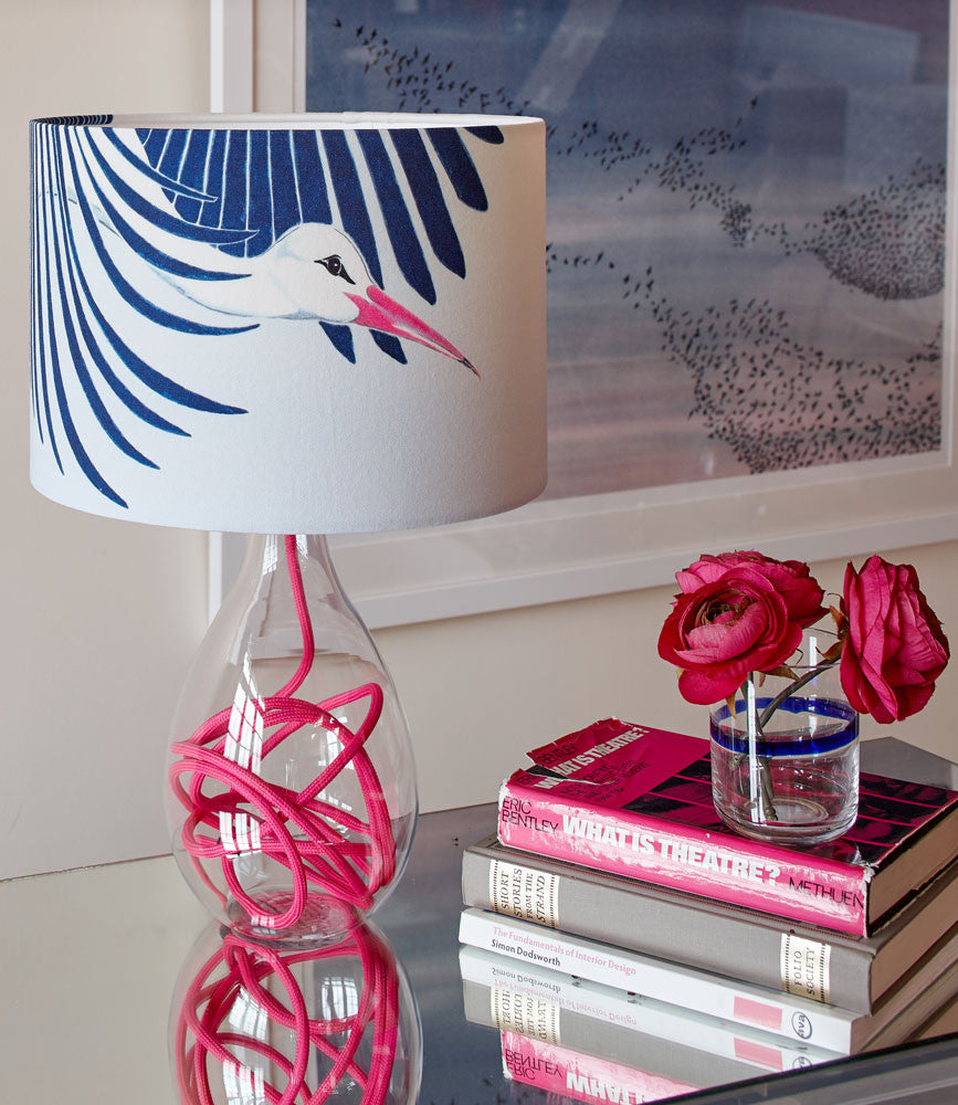 Snow Peak Unbound medium lamp with raspberry flex on a mirrored table with pink flowers and books