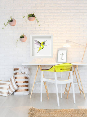 Hummer in yellow framed print 50cm x 50cm hung above a white desk with a yellow chair - by artist Anna Jacobs