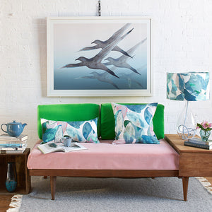 Anna Jacobs Falling leaves in Winter linen bolster lifestyle image on sofa with lamp and Breathe print on wall