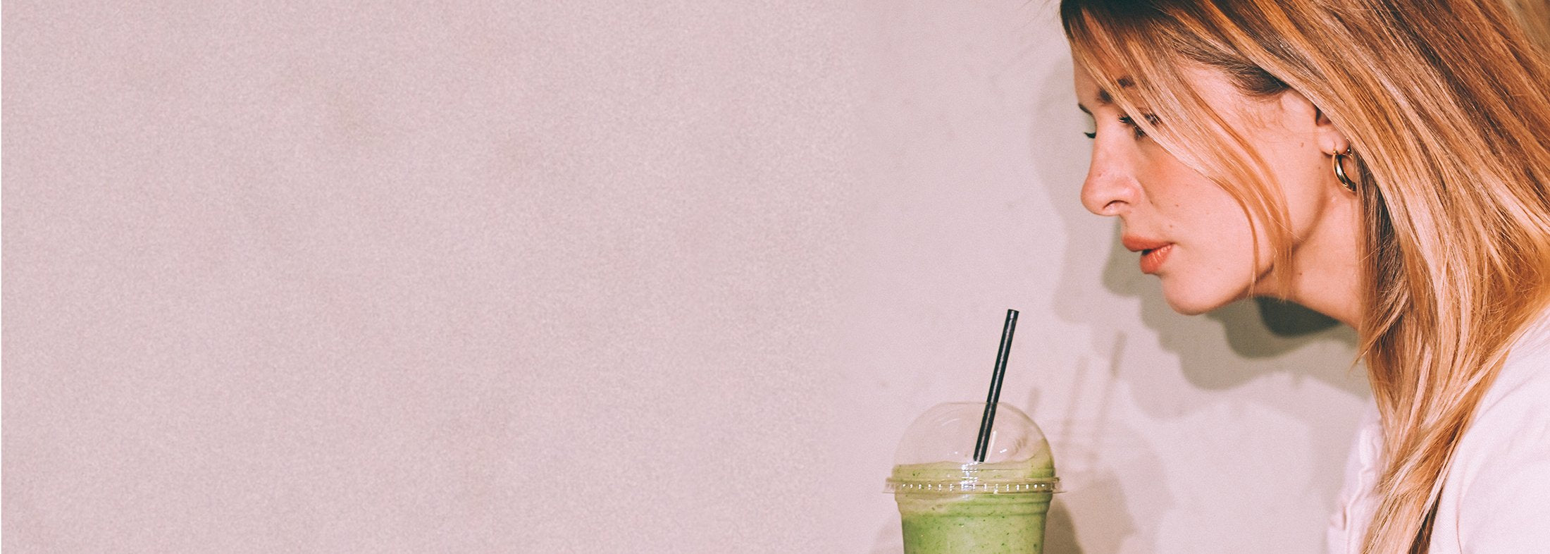 Woman drinking healthy smoothie to combat hormonal hair loss