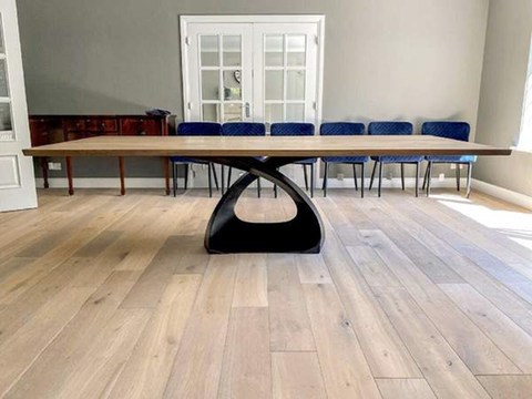 A Long Wooden Tabletop Sporting A Metal Base, Placed in A Room Lined by Chairs and A Chest of Drawers at the Back