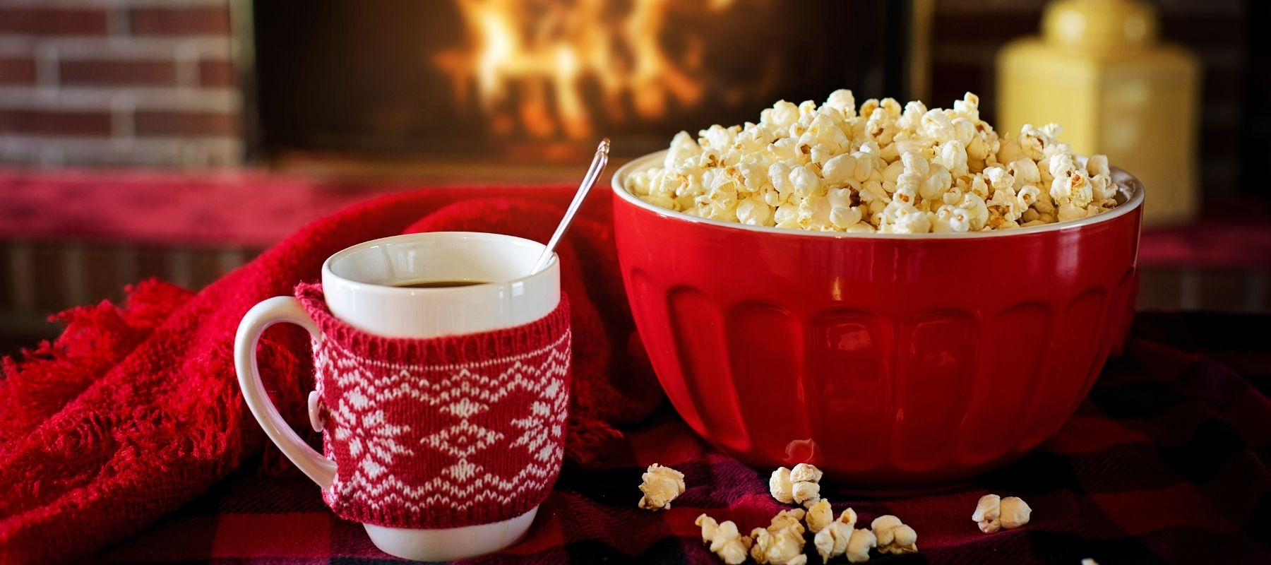 Hot cocoa and popcorn beside a warm fire during the holiday season