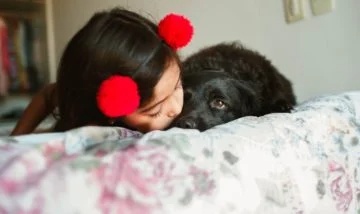 A girl and her dog on the bed