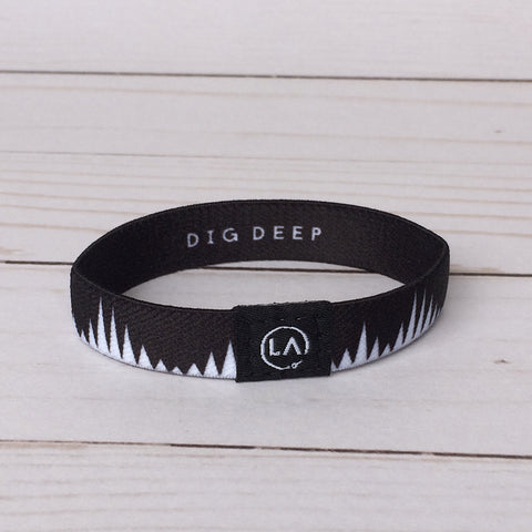 "black and white elastic wristband with words ""dig deep"""
