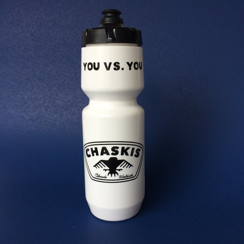 "White plastic sports bottle with black cap; top of bottle reads ""you versus you"" in black lettering, bottom of bottle bears the CHASKIS logo in black"