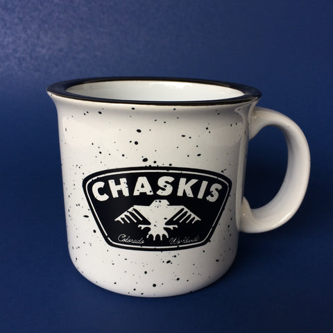 A large, white, coffee mug with black speckles and a black CHASKIS logo