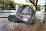 Side view of black and gray CHASKIS original trilife design trucker hat with gray net back, plastic adjustable band and black hat bill