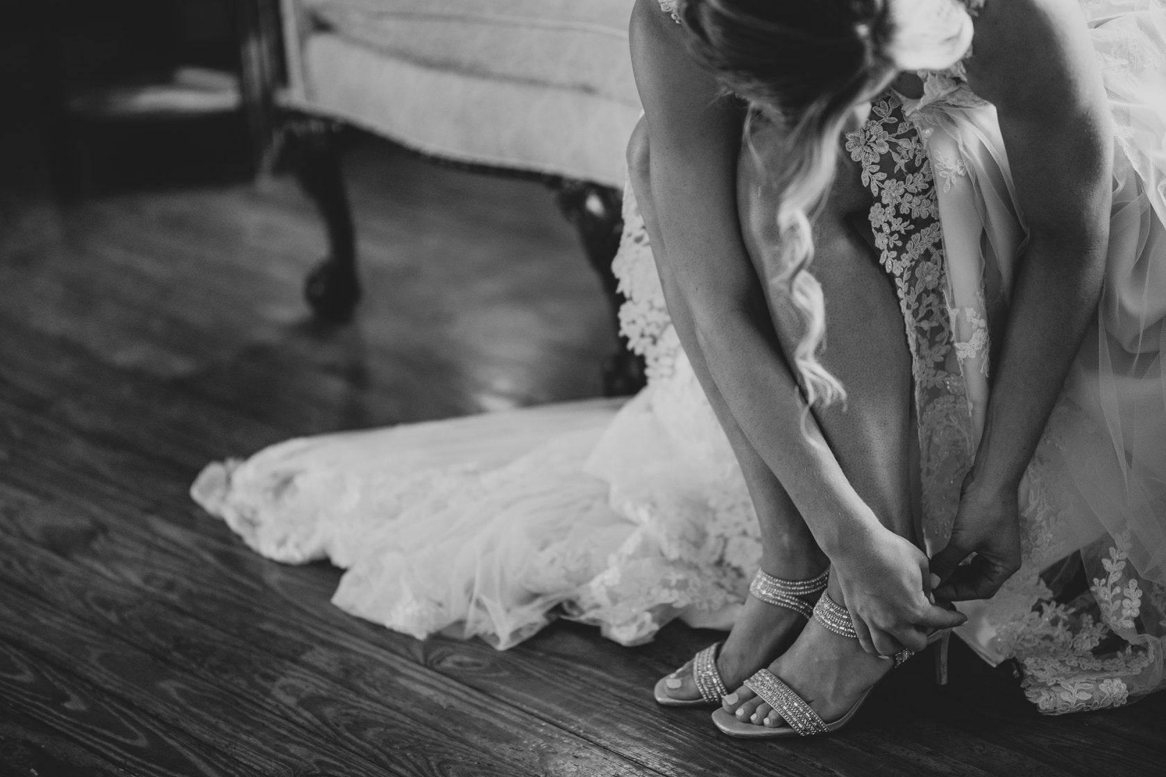 Black and white photo of a bride bending to buckle up her shoe