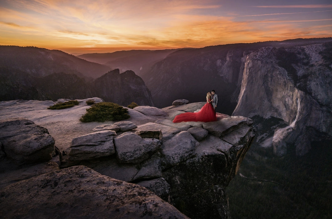 Dramatic photo of a couple posing for an engagement session on the edge of the cliff