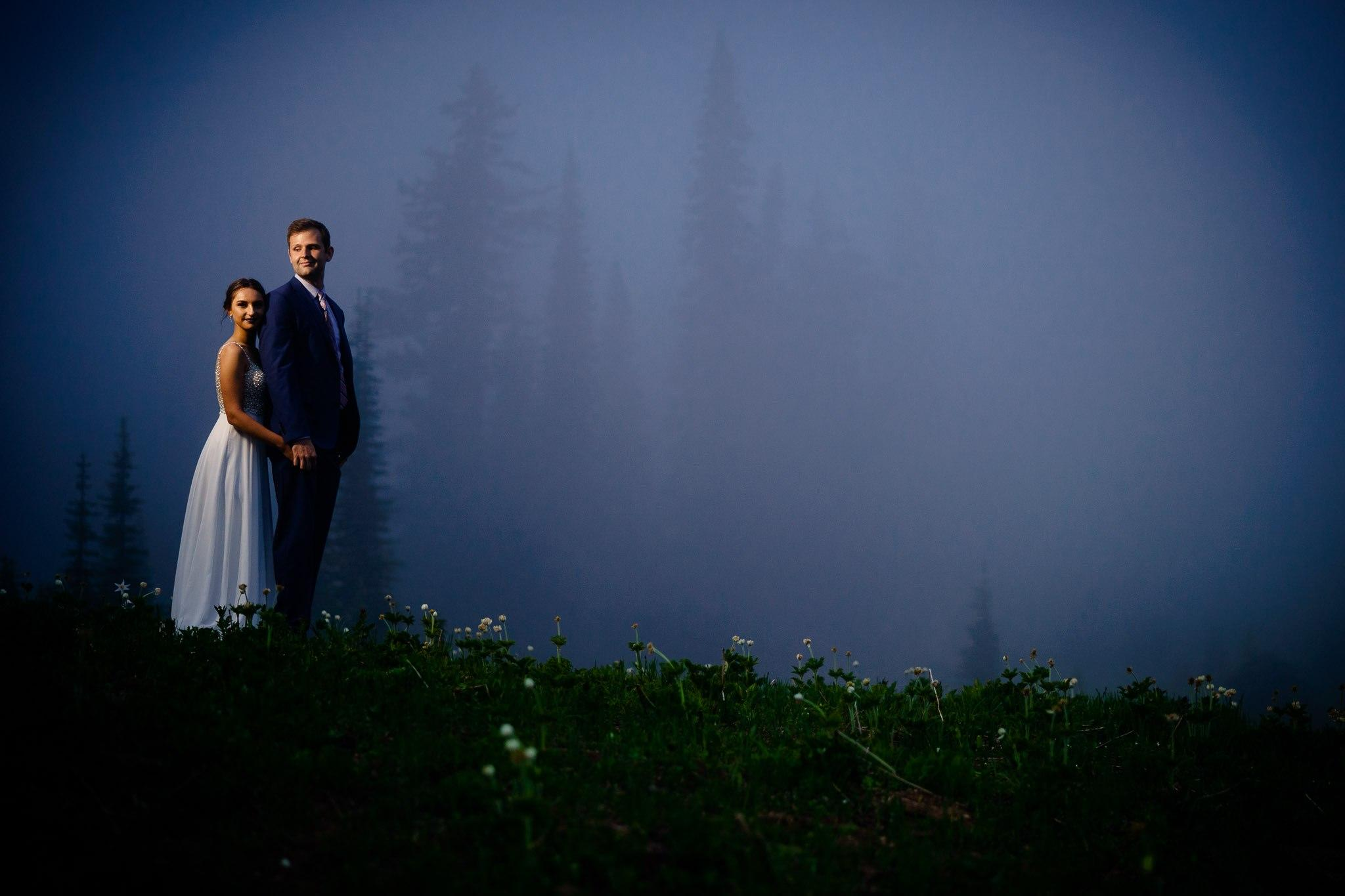 A foggy evening wedding shot with the couple standing on a hill. Edited by ShootDotEdit.