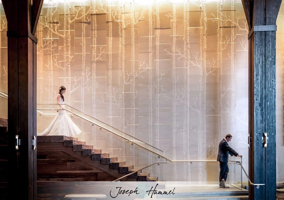 Bride walking down the stairs as the groom waits on the other side in a first look photo as a wedding photography trend 2021