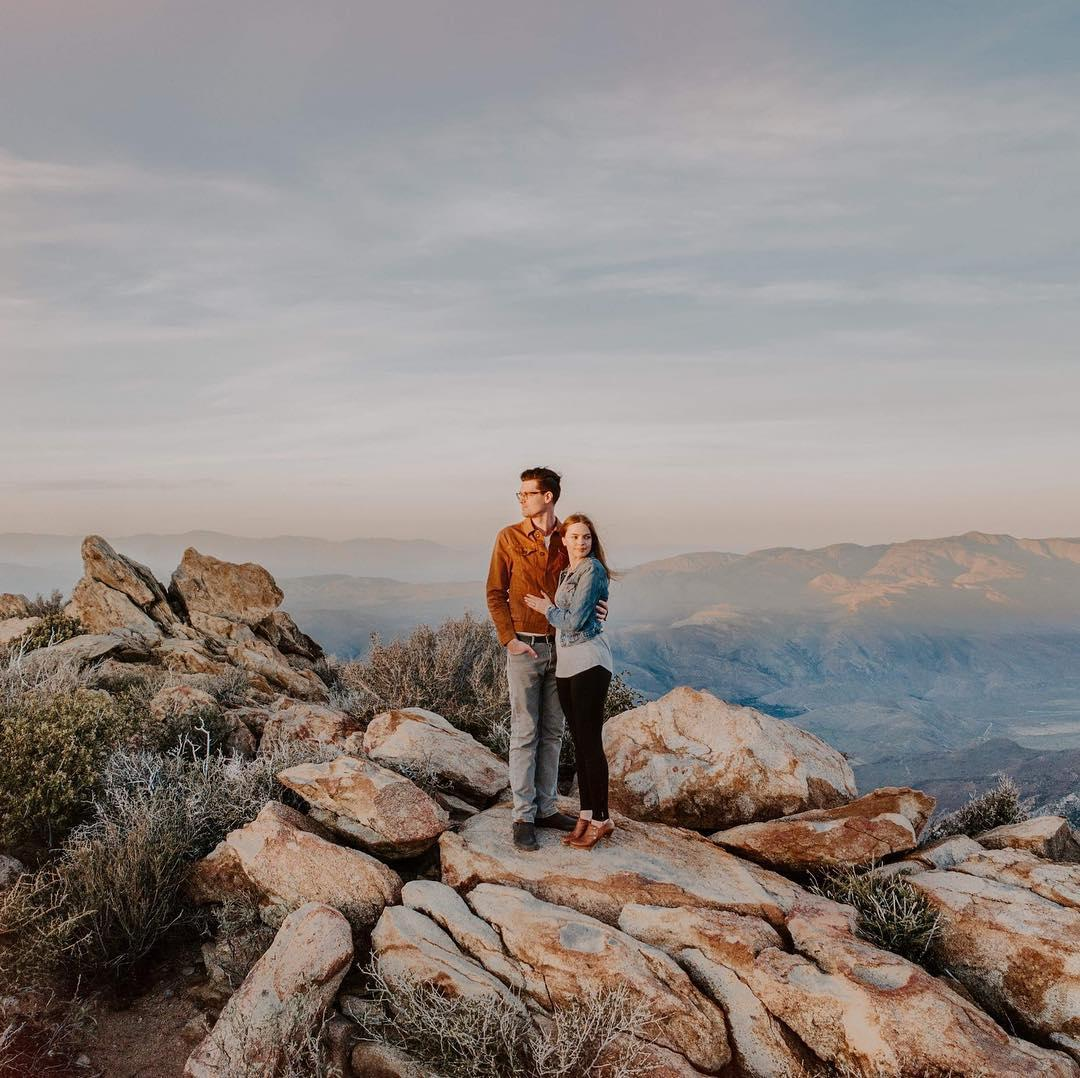 man and woman standing on rocks with a canyon behind them