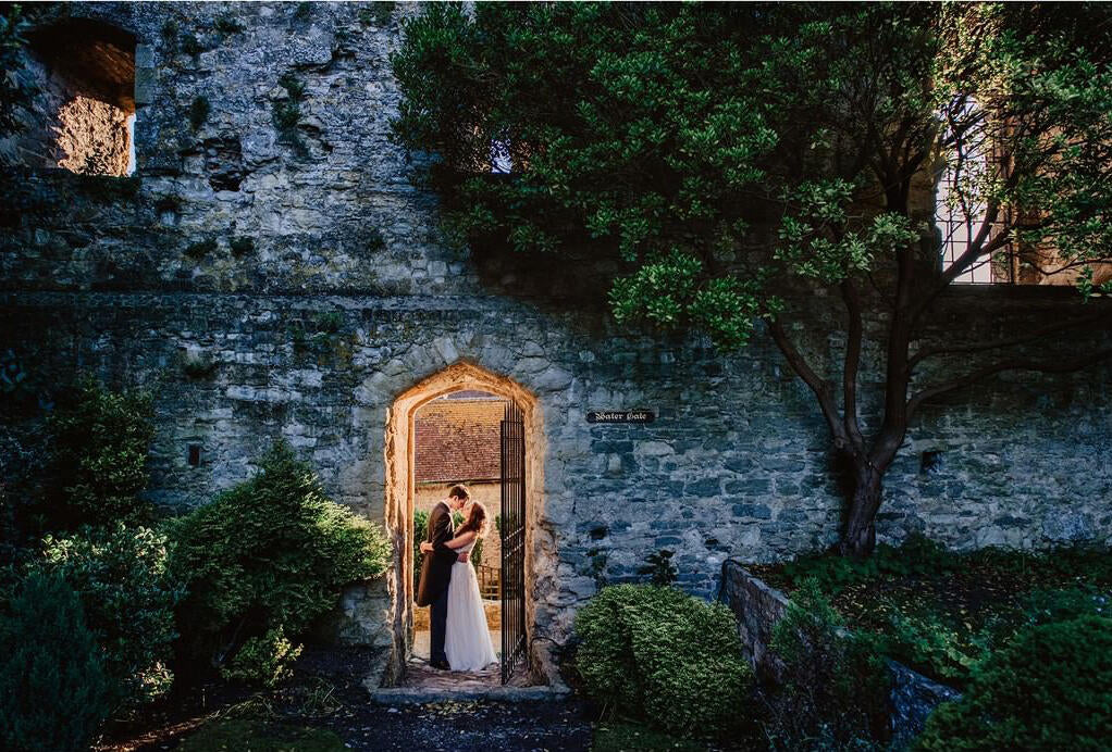 couple in old house doorway lit from behind