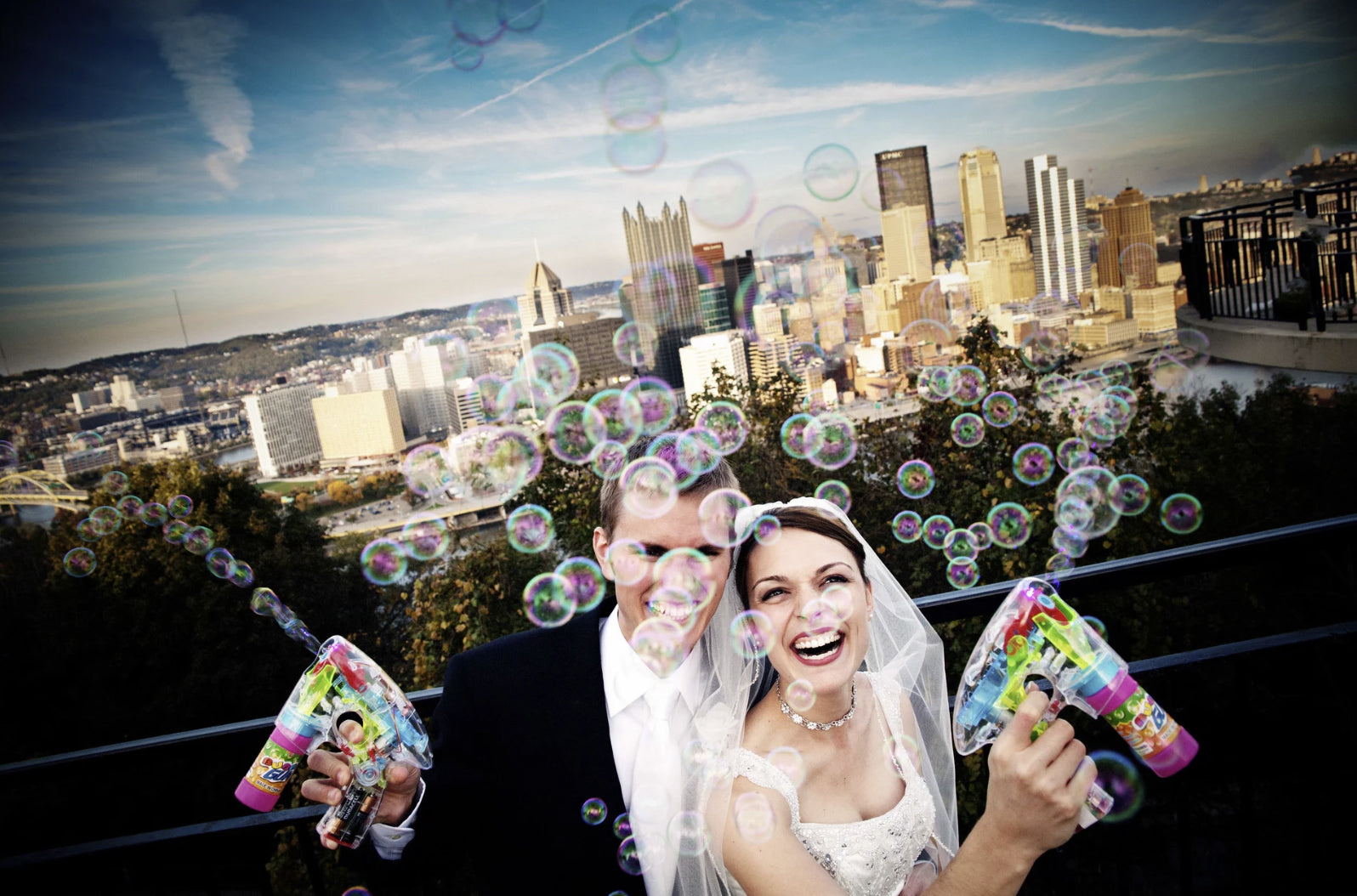 Bride and groom blowing bubbles from bubble-making guns
