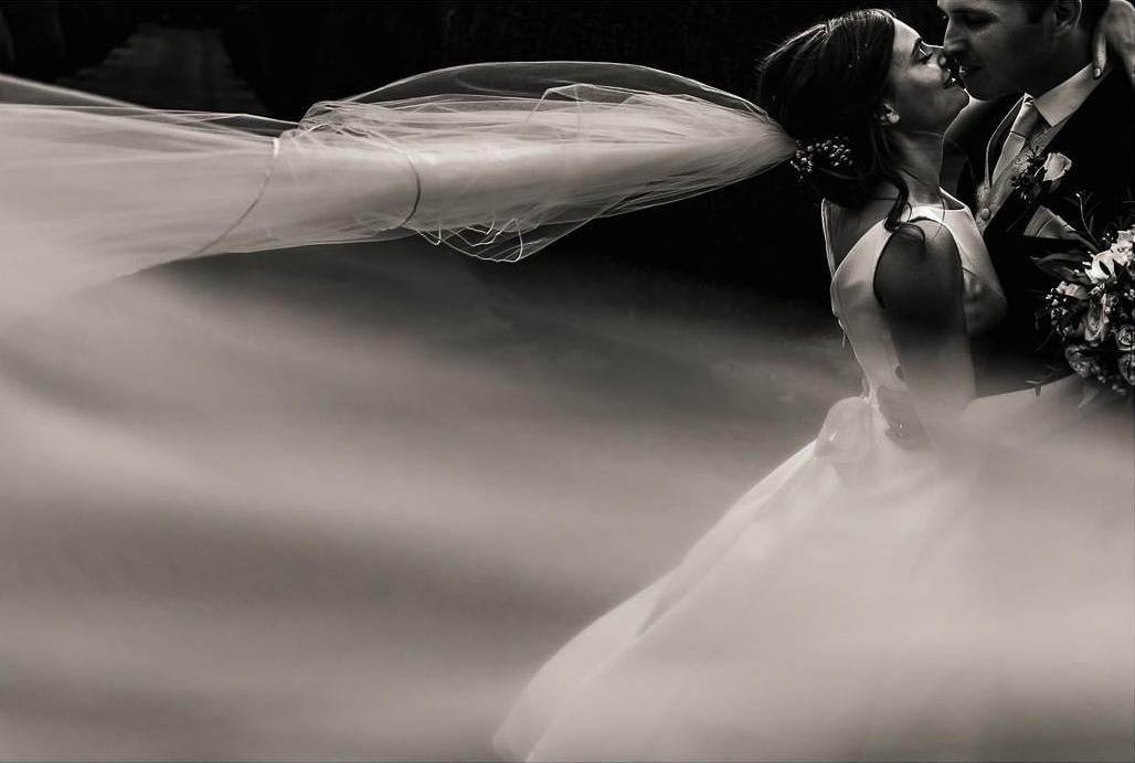 A bride's veil blowing in the wind after the ceremony — kissing her husband. Photo edited by ShootDotEdit.