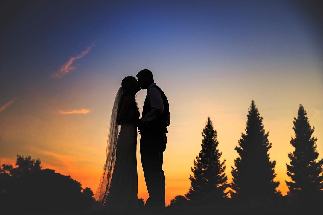 Silhouette of a bride and groom kissing with trees in the background