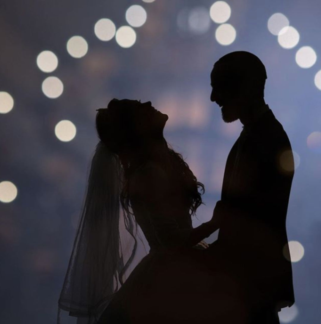 Silhouette of the bride and groom as they hold each other with a bokeh background