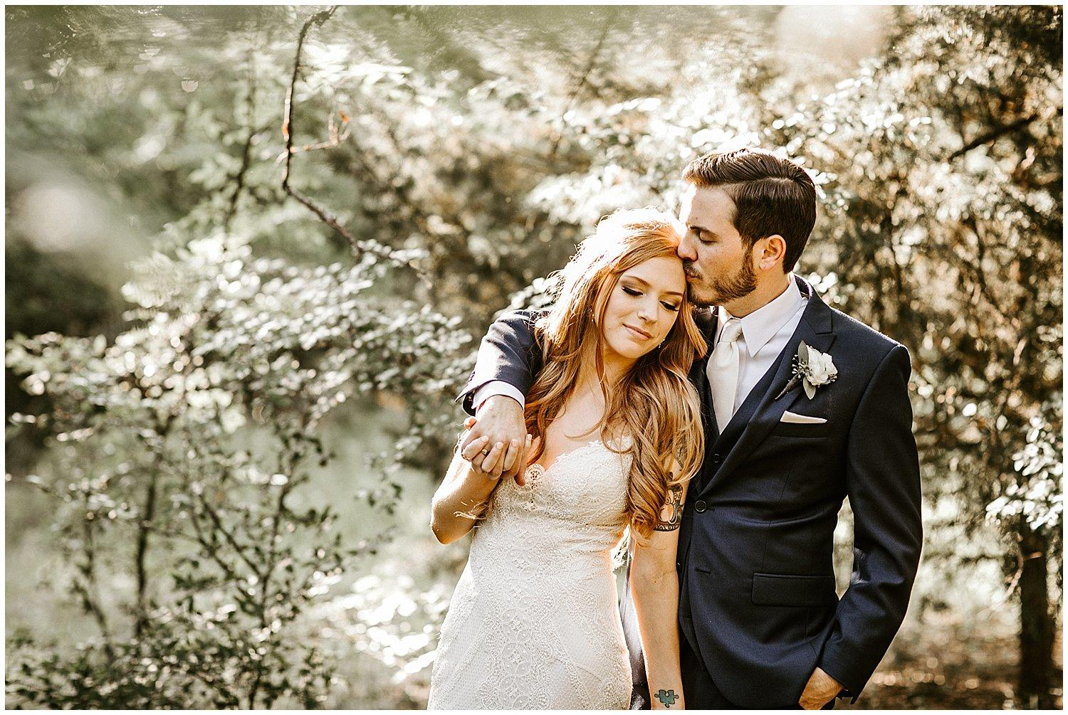 A wedding couple standing in the woods, in love. Brandi Allyse Photography