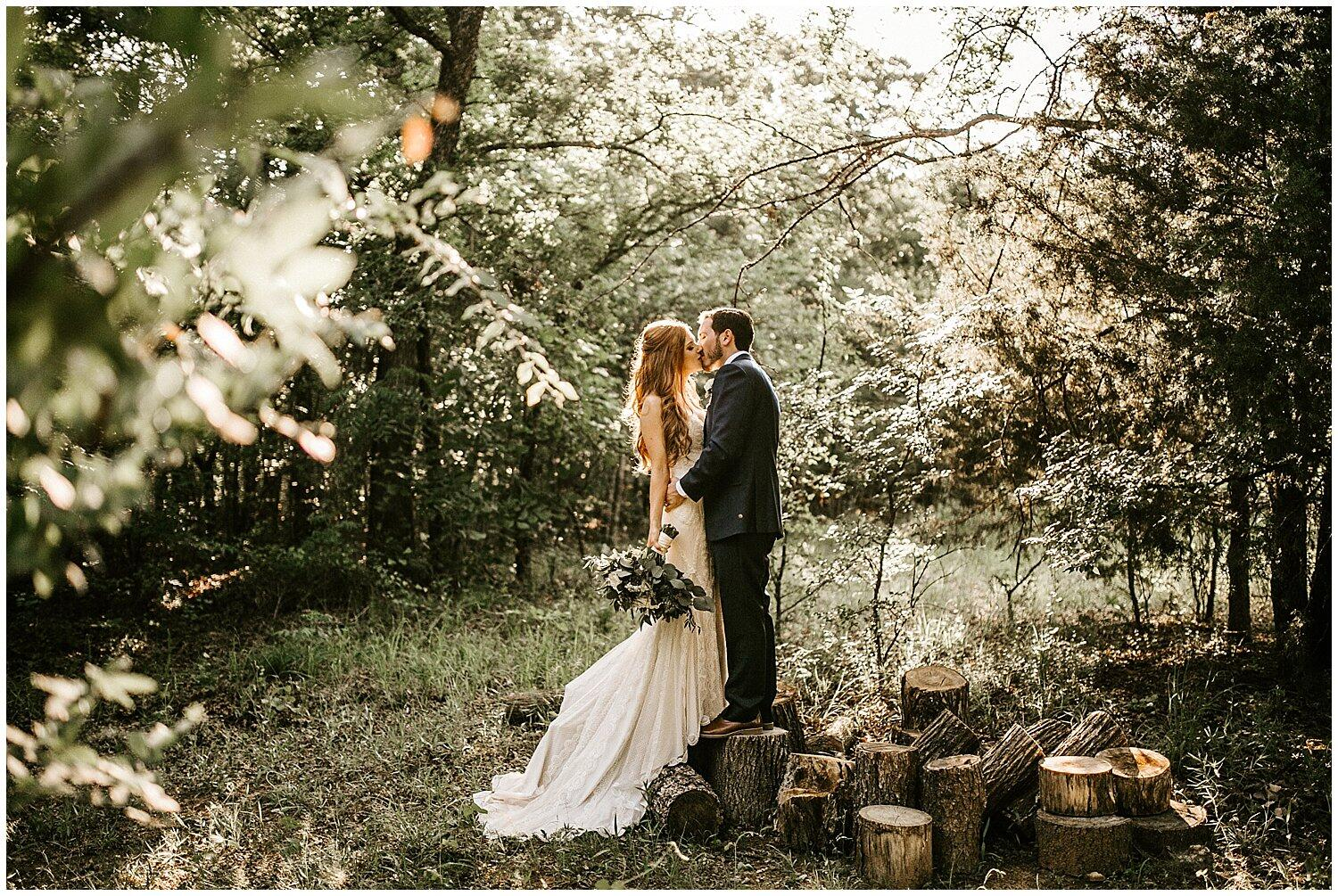 Bride with a bouquet in hand and groom holding the bride pose for a kiss in the wild