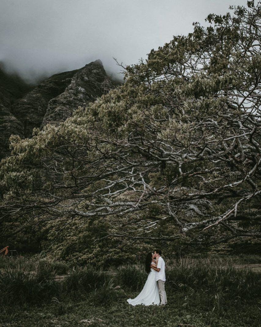 dark and stormy night in Hawaii with couple kissing under big tree